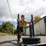 athletic-man-exercising-with-sled-outside-gym-royalty-free-image-1056425154-1551576538